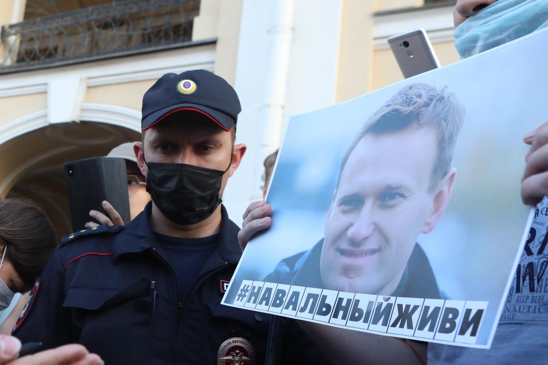 Een politieagent loopt af op een demonstrant met een bordje