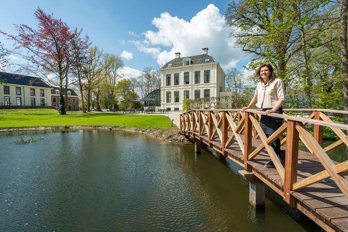 Inge van de Ven, eigenaresse van hotel Flora Batava. Achter haar de gerestaureerde villa, met daarin acht hotelkamers en het restaurant. Links de twee andere gebouwen op het terrein met hotelkamers.