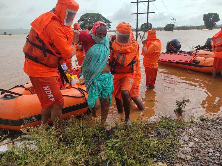 Reddingswerkers helpen dorpsbewoners in de Indiase staat Maharashtra, dat zwaar getroffen werd door hevige moessonregens. Beeld EPA