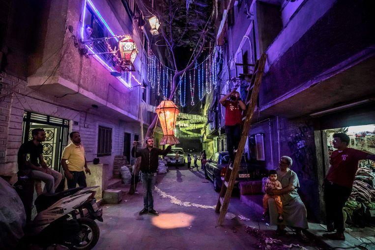 Egyptische jongeren versieren hun buurt in Caïro ter voorbereiding van de vastenmaand. Beeld AFP