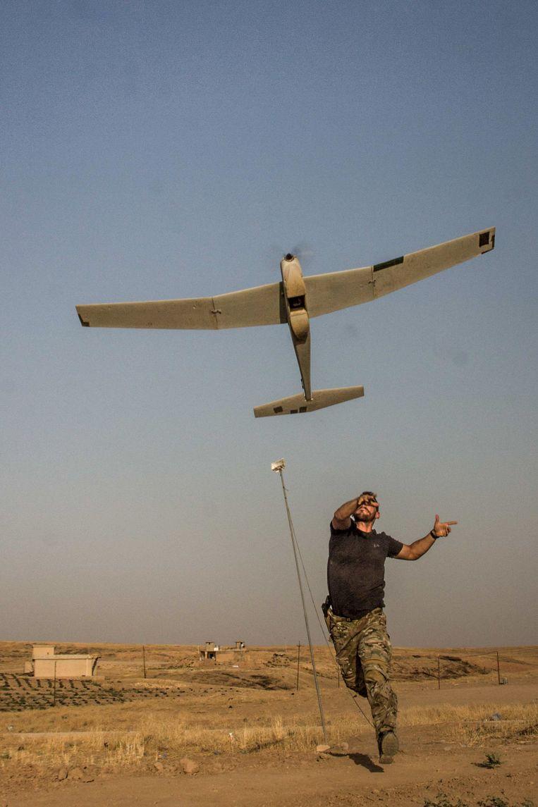 Een Belgische militair lanceert een Puma-dronevliegtuigje. Daarmee observeerden ze de IS-schietposities.  Beeld RV