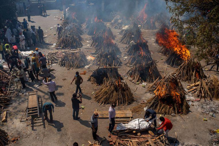 Meerdere mensen die zijn overleden aan het coronavirus worden verbrand tijdens een massacrematie in Delhi.  Beeld AP