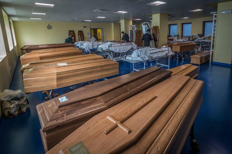 In lakens gepakte lichamen staan klaar in een ziekenhuismortuarium om in lijkkisten gelegd te worden. In de regio Bergamo zijn al tweeduizend coronadoden geteld. Beeld Photo News