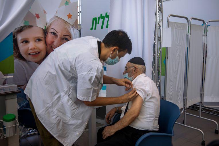 Een Israëlische man ontvangt een Pfizer-'booster' in Tel Aviv. Beeld AP