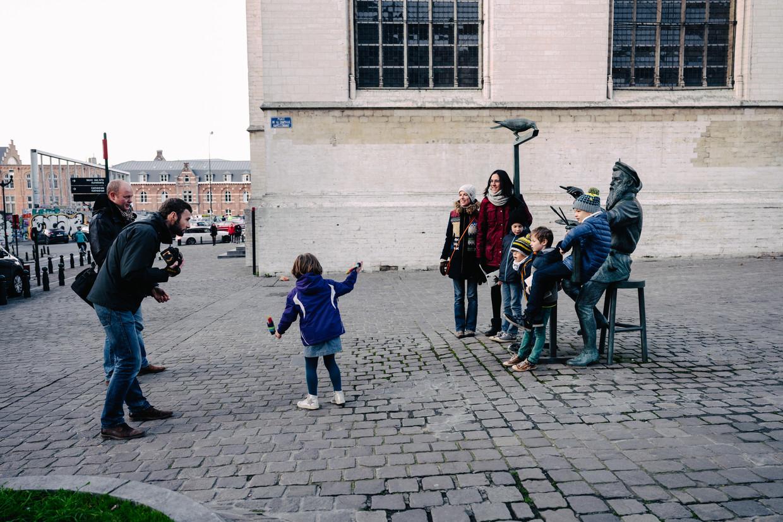 Toeristen in Brussel aan het standbeeld van Tom Frantzen dat Bruegel uitbeeldt aan zijn schildersezel.