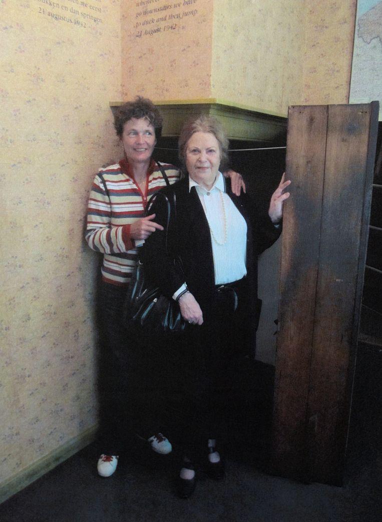 Diny Voskuijl (met een vriendin) bij de wereldberoemde boekenkast die haar vader heeft getimmerd. Beeld Gerard Wessel