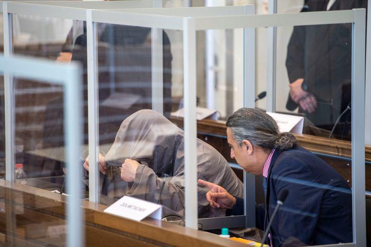 Verdachte Eyad A. verbergt zijn gezicht in de rechtszaal. Beeld Thomas Lohnes/AFP Pool/dpa