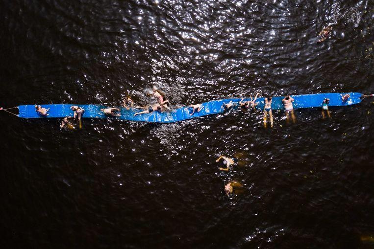 Luchtfoto van zwembad de Meent in Breukelen, waar mensen verkoeling zoeken op het water.  Beeld ANP