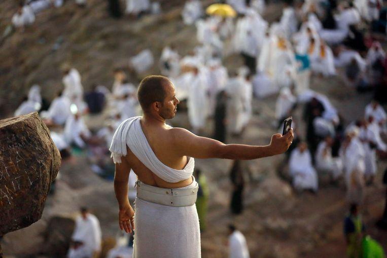 Een pelgrim neemt een selfie op de berg Arafat.