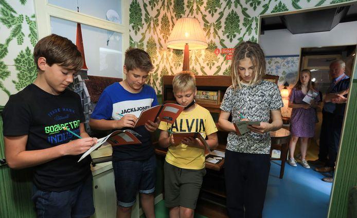Sander, Bart, Denzel en Teim maken hun opdrachten in de museumtrailer.