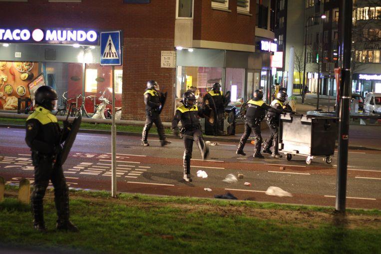 Leden van de ME op straat in Enschede. Een groep mensen protesteert daar tegen de avondklok. De sfeer is grimmig. Beeld ANP