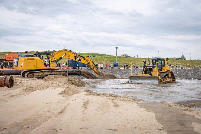 Onder aanzienlijke publieke belangstelling wordt het strand bij Zoutelande opgespoten. Soms worden mensen wat al te nieuwsgierig naar de werkzaamheden.