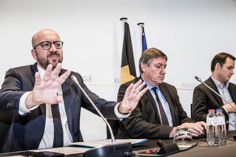 Premier Michel en zijn vicepremiers Jambon en De Croo delen de beslissing van de Veiligheidsraad mee. De dreiging blijft 'aanwezig en zeer nabij'. Beeld Bob Van Mol