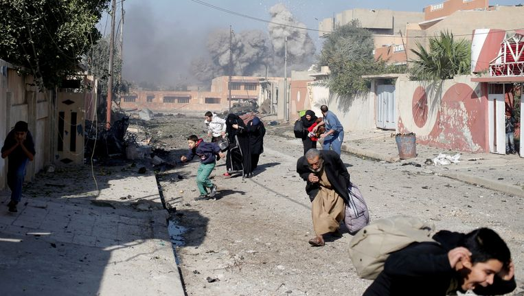 Mensen vluchten voor een luchtaanval tegen terreurgroep IS in Mosul, Irak.