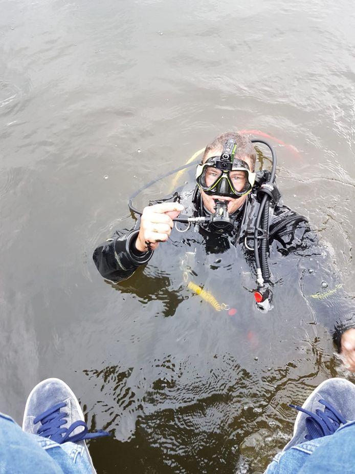 Spijkenisser Martin van Hees duikt een ring op uit het water.