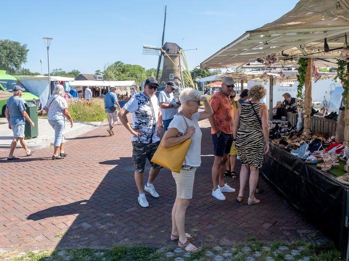 De weekmarkt trekt op het parkeerterrein bij de molen in Domburg heel wat meer publiek dan op het terrein achter het gemeentehuis.