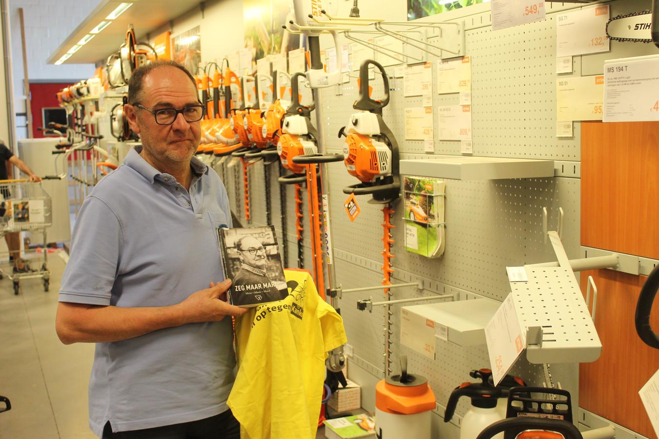 Marc Van Wiemeersch met zijn boek tussen de rekken van zijn doe-het-zelfzaak.