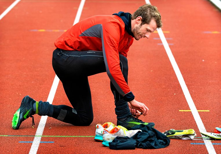 Atleet Thijmen Kupers doet zijn spikes aan op de atletiekbaan in het Stadspark in Groningen. Beeld Klaas Jan van der Weij