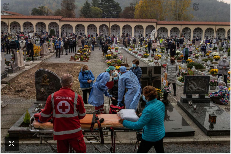 Mensen van het Rode Kruis bekommeren zich op het kerkhof van Nembro om een vrouw die tijdens een mis ter herdenking van covidslachtoffers was flauwgevallen. Beeld NYT/Fabio Bucciarelli