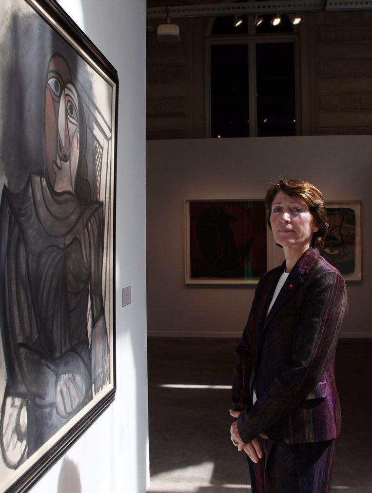 Marina Picasso bij het werk van haar vader 'Femme assise en robe grise'. Beeld afp