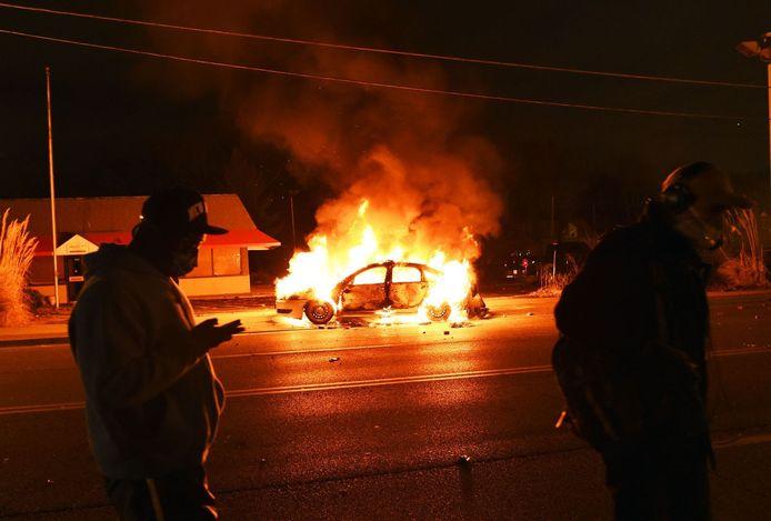 Een politieauto gaat in vlammen op in Ferguson.