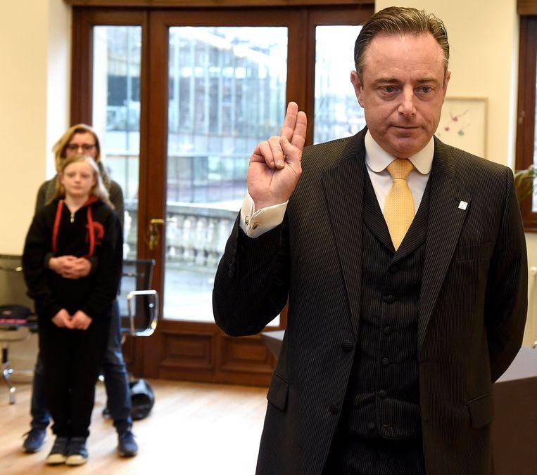 Bart De Wever legt de eed af bij Gouverneur Cathy Berx. Op de achtergrond staan zijn vrouw Veerle en dochter. Beeld Photo News