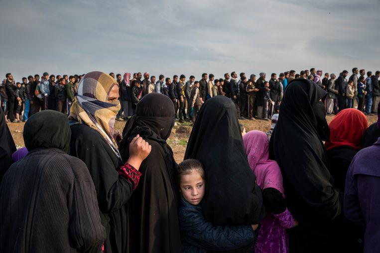 Gevluchte inwoners uit Mosul staan in de rij voor hulpgoederen, in maart 2017. De stad is het decor van zware gevechten tussen IS en het Irakese leger.  Beeld NYT