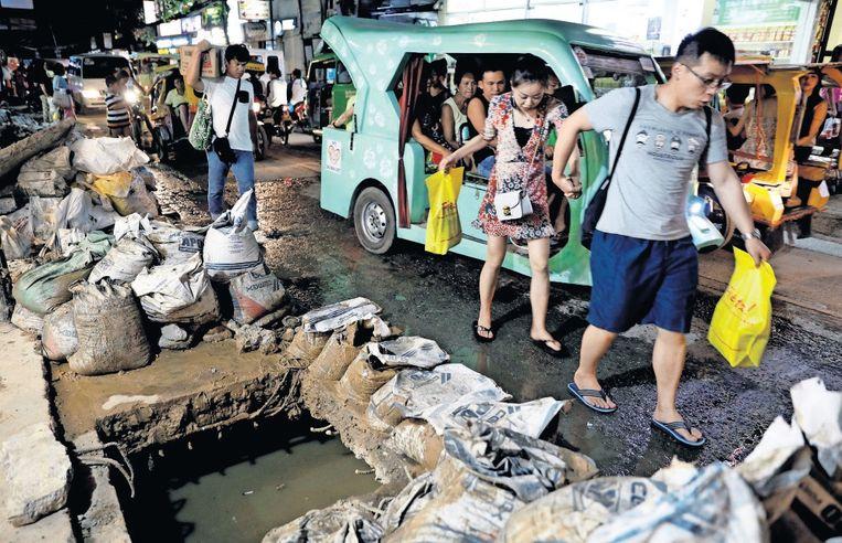 Toeristen passeren een gat in het riool en achtergelaten zakken vuilnis. Beeld Reuters