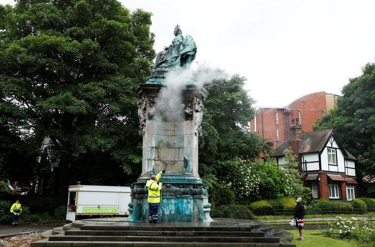 Het beeld van de Britse Queen Victoria wordt opgekuist nadat het werd beklad in Woodhouse Moor, Leeds. Er werd onder meer 'racist' en 'slaveneigenaar' op gespoten. Tijdens haar regeerperiode groeide het Britse rijk uit tot een wereldmacht, met verscheidene kolonies. Beeld REUTERS
