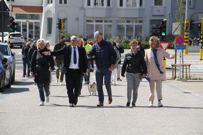 Een delegatie van het gemeentebestuur wandelt de Duinbergenlaan in.