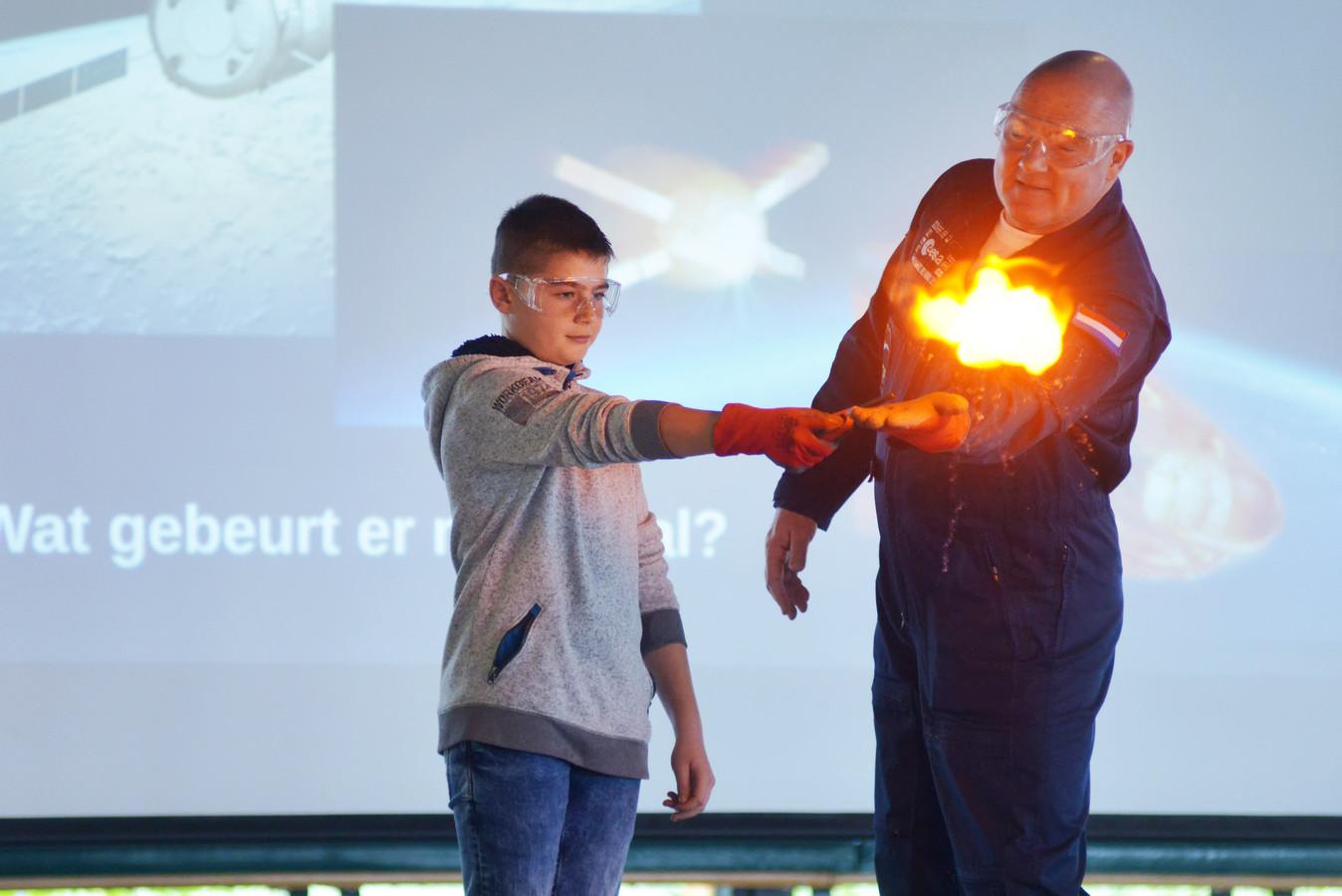 André Kuipers laat met hulp van een leerling van de Sint Agnesschool zien hoe je afval in de ruimte verbrandt.