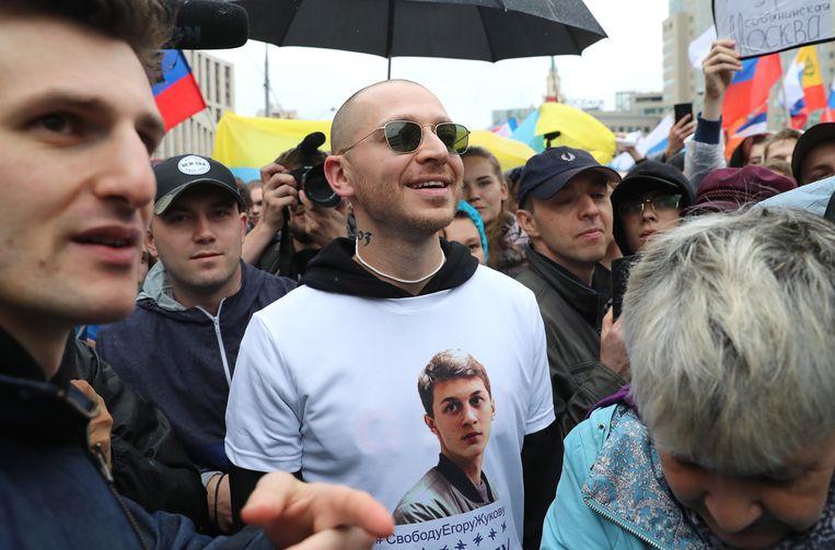 Rapper Oxxxymiron tussen de demonstranten in een T-shirt met het portret van Jegor Zjoekov. Beeld Getty Images