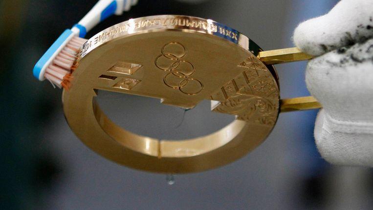 Een medewerker poetst een bronzen medaille voor de Winterspelen in 2014. Beeld REUTERS