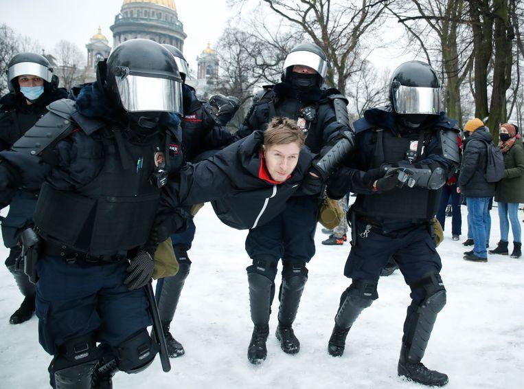 De politie houdt een man vast tijdens de protesten in Sint-Petersburg. Beeld AP