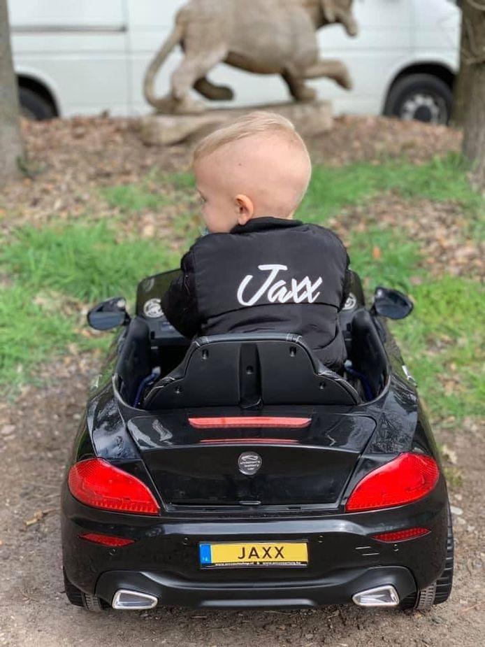 Jaxx in een speelgoedauto.