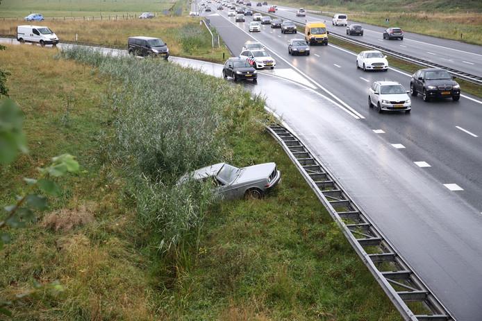 De auto ligt langs de A15 in de berm.