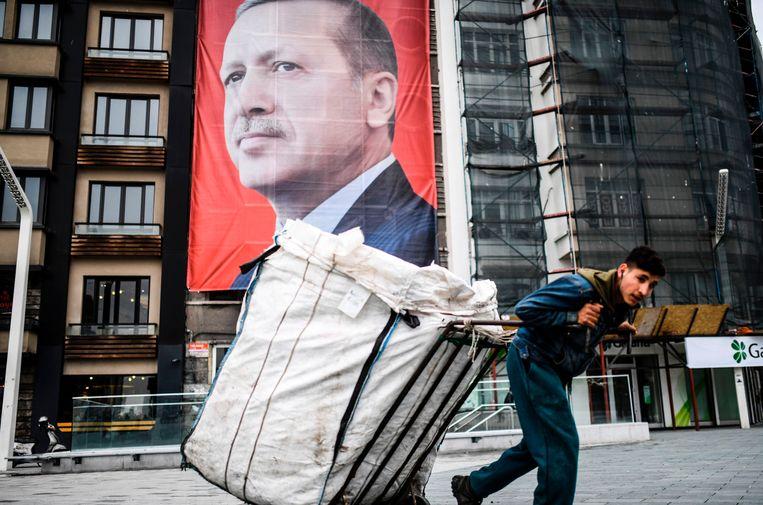 Een man trekt een kar voort in Istanbul, met op de achtergrond een portret van de Turkse leider Erdogan. Orhan Pamuk: