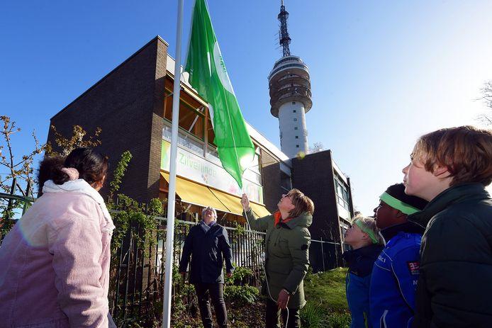 Basisschool Zilverlinde is Eco-school en mag de Groene Vlag hijsen. Wethouder Klaar Koenraad kijkt toe.
