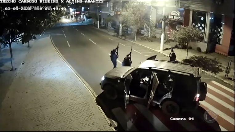 Overvallers schieten in de lucht, vastgelegd door een beveiligingscamera.  Beeld