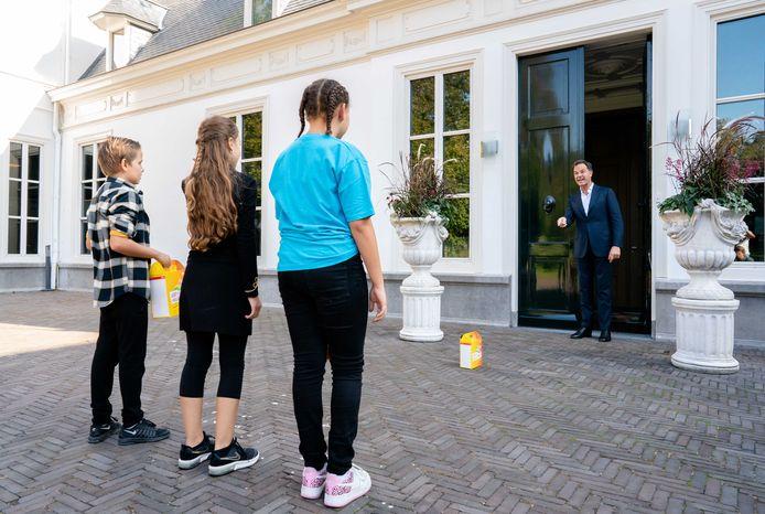 Julian (10), Safa (11) en Emmaly (11) bellen bij het Catshuis aan om de eerste kinderpostzegels te verkopen aan premier Mark Rutte.