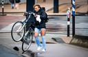 Een fietser trotseert de harde wind op de Erasmusbrug in Rotterdam.