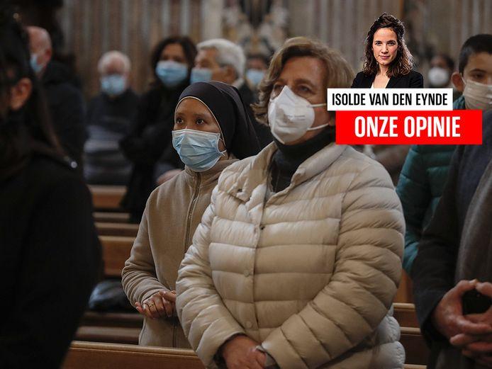 Mensen wonen met mondkapjes een katholieke mis bij in Italië. Archiefbeeld.