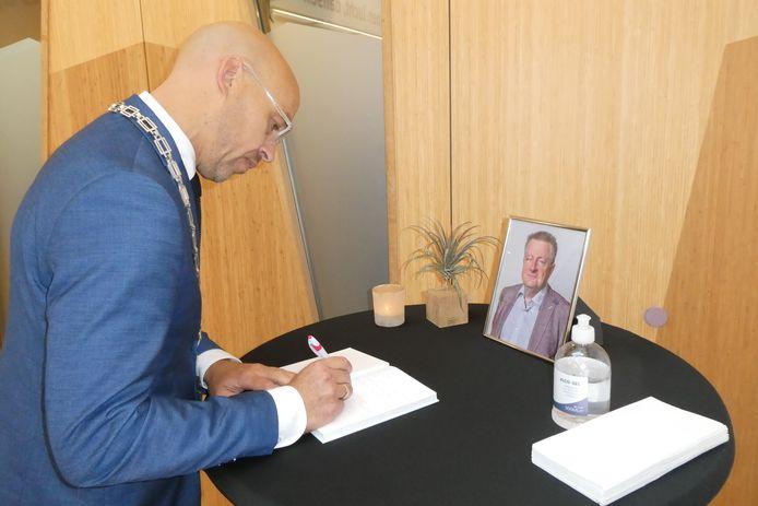Burgemeester Han Looijen tekent het condoleanceboekje voor het overleden PvdA-raadslid Jack de Vlieger.