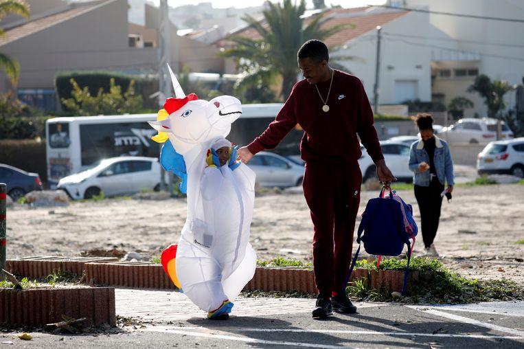 Een vader begeleidt zijn zoontje in een eenhoornpak naar school. De leerlingen in Ashkelon, Zuid-Israël, mogen allemaal verkleed komen aan de vooravond van Poerim, een uitbundig voorjaarsfeest dat carnavaleske trekken heeft.  Beeld Reuters