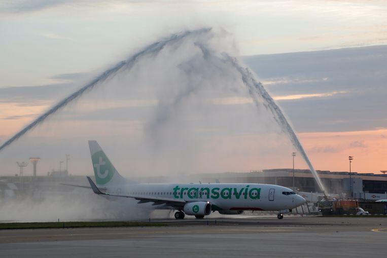 Brandweervoertuigen op het vliegveld van Orly spuiten water over een Transavia-vliegtuig om te vieren dat het toestel weer de lucht in kan, na de eerste lockdown in juni vorig jaar. Beeld Reuters
