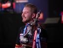 Een stralende Dimitri Van den Bergh omklemt de reusachtige bokaal na zijn winst in de finale van de World Matchplay.