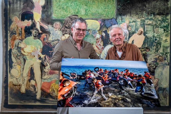 Kunstenaar Stijn Peeters (l) en fotograaf Piet den Blanken exposeren samen bij Pennings Foundation in Eindhoven. In hun handen houden ze een foto van Den Blanken uit 2015. Hij maakte de foto op het Griekse eiland Lesbos, onderdeel van de Balkanroute, het belangrijkste traject voor vluchtelingen uit Syrië, Afghanistan en Pakistan. Op de achtergrond het schilderij 'A Study Of Values' van Peeters.