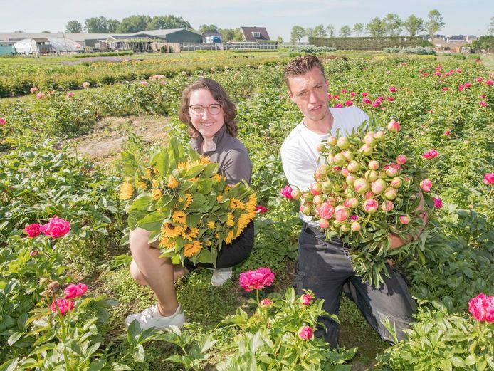 Inge Jansen met zonnebloemen en Adriaan Jansen met de Coral Red Sun pioenrozen.
