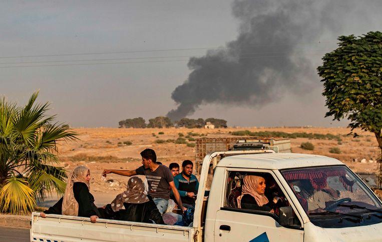Burgers in een wagen terwijl op de achtergrond de rook opstijgt na een Turks bombardement in de Syrische grensstrook.  Beeld AFP
