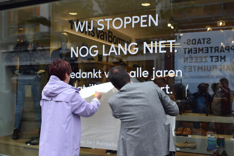 Karine Valy (zaakvoerster La Bottega) en Danny Van Assche (gedelegeerd bestuurder UNIZO) hangen de 'Winkelhier'-campagne op. Beeld BELGAONTHESPOT